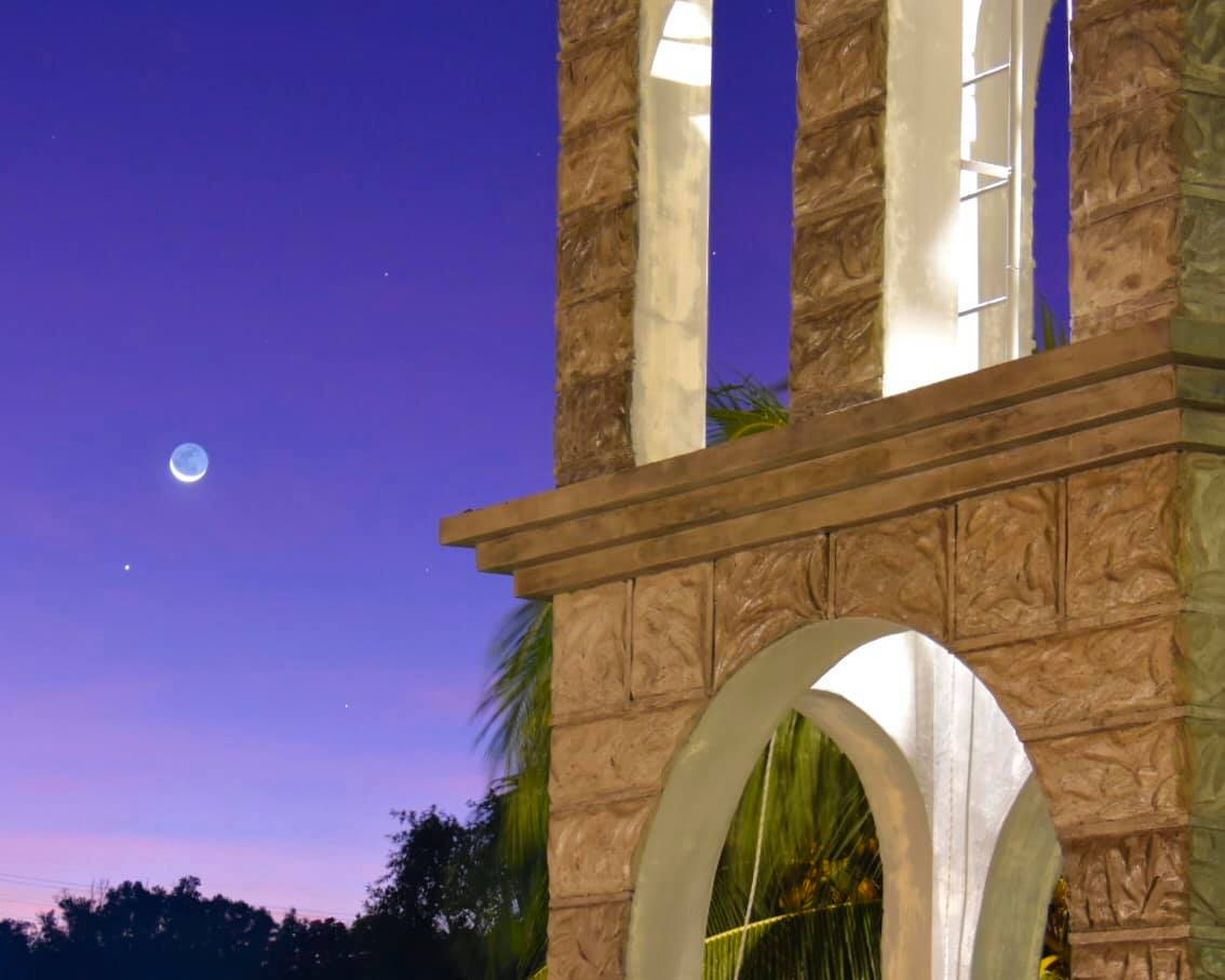 Moon and tiny starlike dot and an arched stone structure against purple sky.