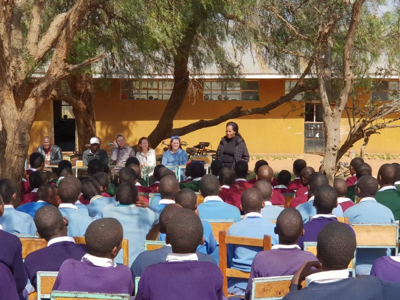 Team of scientists addressing an outdoor classrom with many local children.