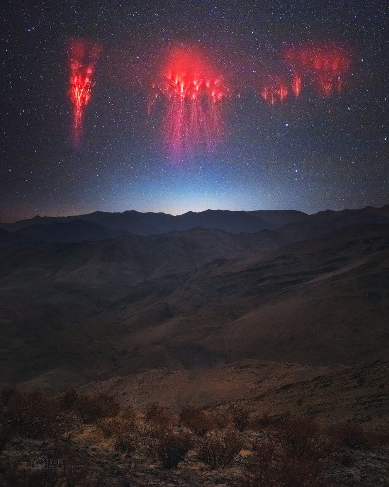 Dark sky with 3 fluorescent pink blobs wiht red lightning trailing down from them over mountains.