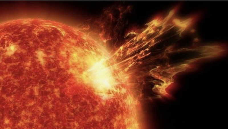 A bright spot on the sun's surface that is sending a bright orange glowing stream of particles into space.