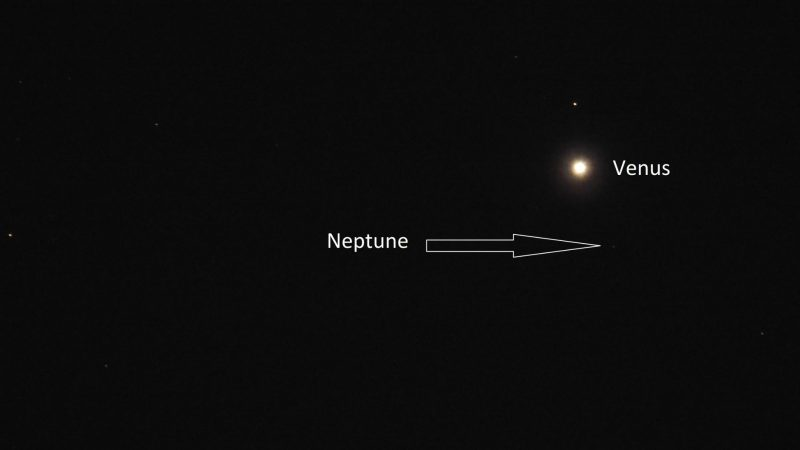 Venus with a star close to it and a big arrow pointing to nearly invisible Neptune.