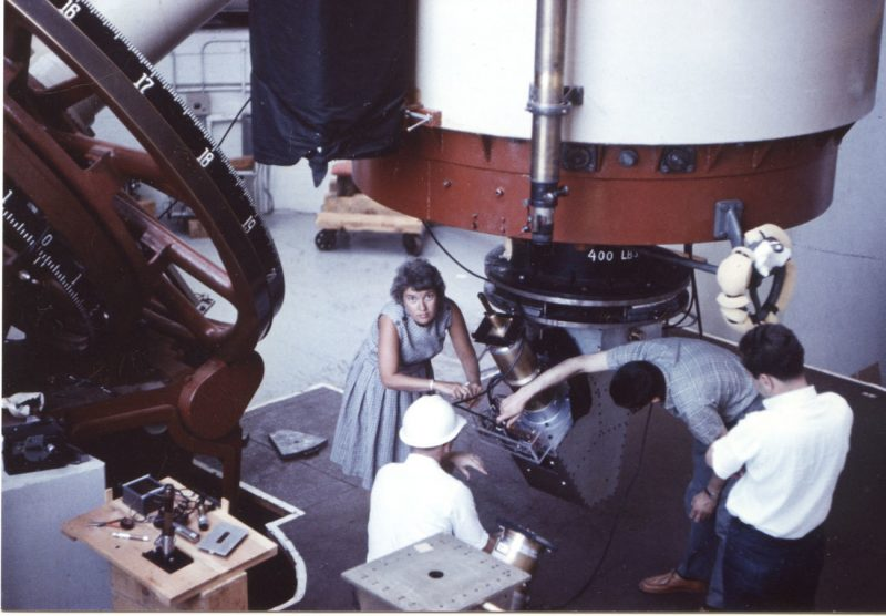 A young female astronomer in a dress, working at a huge telescope, surrounded by male astronomers.