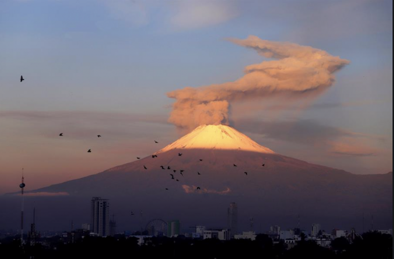 Sunrise is illuminating the upper part of the volcanic cone, which is spewing dense smoke.