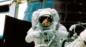 An astronaut holding tools in front of Hubble during the 1997 servicing mission.
