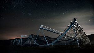Large curving metallic structure under starry sky.