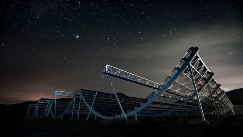 Large curving metallic framework structure under starry sky.