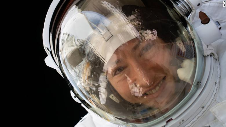Smiling woman in a spacesuit, with black space behind her.