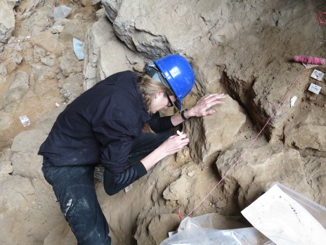 A woman scientist in cave gear and a blue hard hat, chipping at a rock with a small tool.