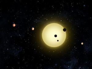 """A yellow sunlike star with 4 planets. Two of the planets are """"transiting"""" or passing in front of the star."""