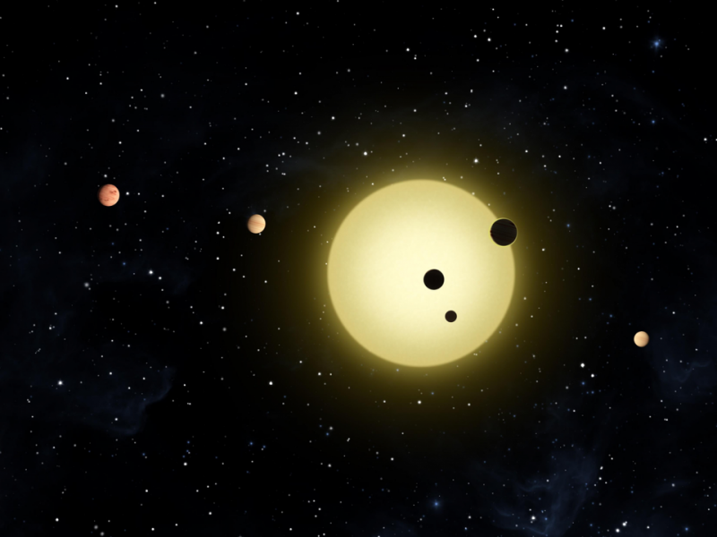 A yellow sunlike star with 4 planets. Two of the planets are 'transiting' or passing in front of the star.
