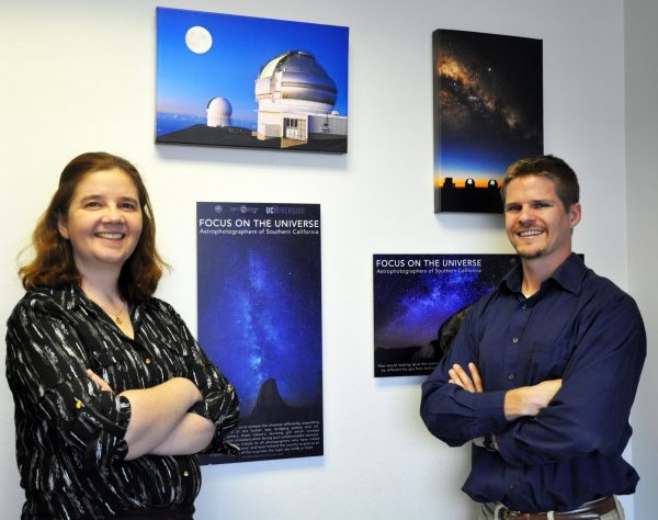 Smiling woman and man, standing in front of pictures of astronomy things.