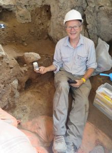 Graeme Baker holding a soil block at the Shanidar Cave excavation site.