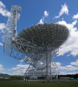 Radio telescope with blue sky and clouds in background.