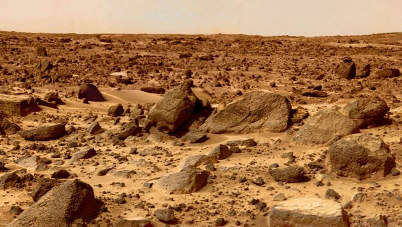 Reddish boulders and sand dunes under pinkish sky.