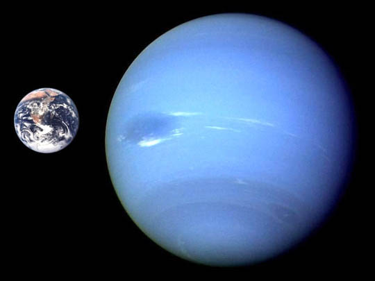 Small Earth next to large blue Neptune on black background.