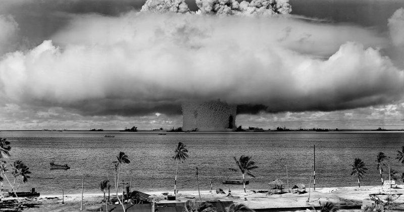 A beach scene, looking seaward at a huge mushroom-like cloud.