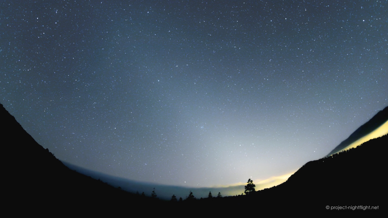 Twilight sky over panoramic horizon with long cone of light from sunset location.