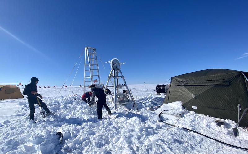 Researchers clearing snow at the drill site.
