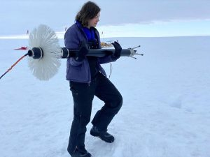 Graduate student Aurora Basinski holds the instrument used for measuring water turbulence.