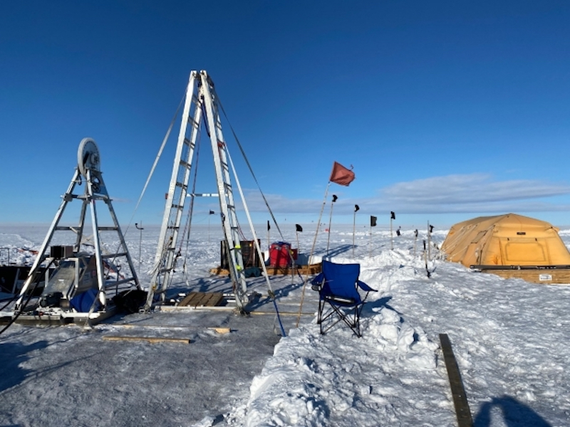 The drill site showing tall drill rigs and a large tent.