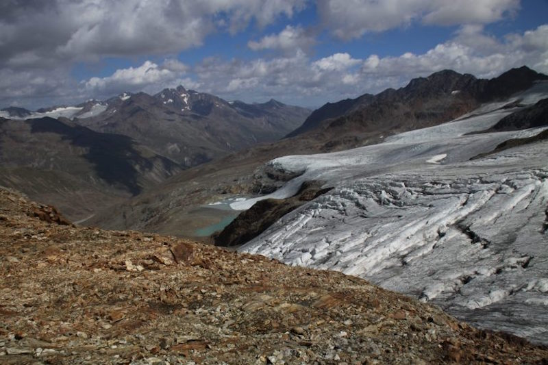 Rocky landscape with snowy mountains in the background and glacier on nearby slope.