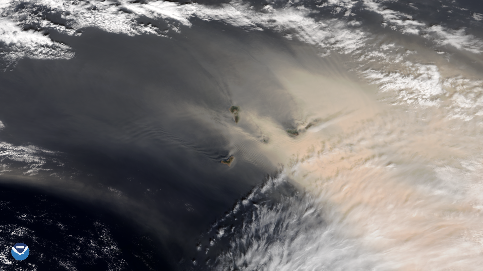 Orbital view of dust over the ocean, with islands barely visible in the dust.