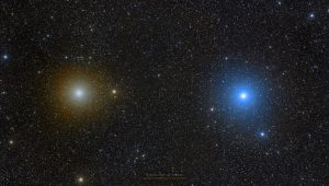 Image of Pollux and Castor. Pollux appears as a light gold star while Castor appears blue-white.