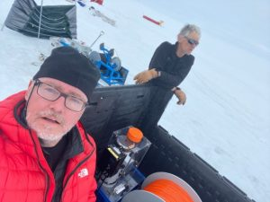 Two scientists in Antactica, with instruments scattered nearby.