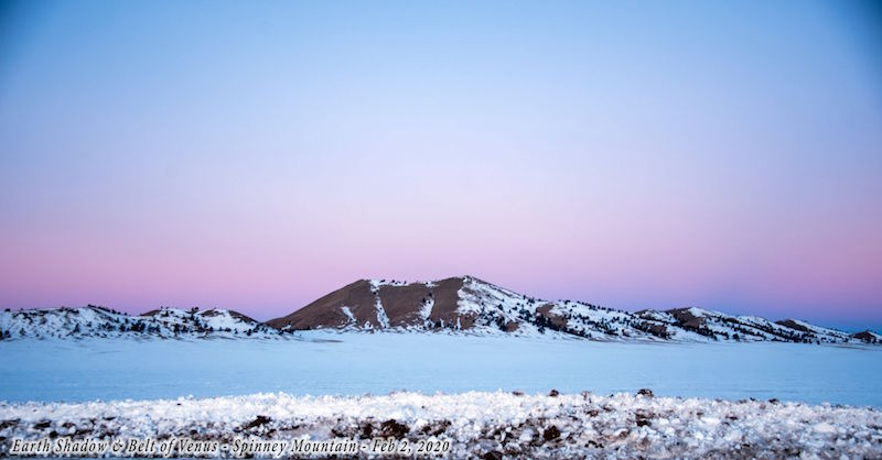 Mountain rising from foggy lowland, against blue sky with a pink stripe,