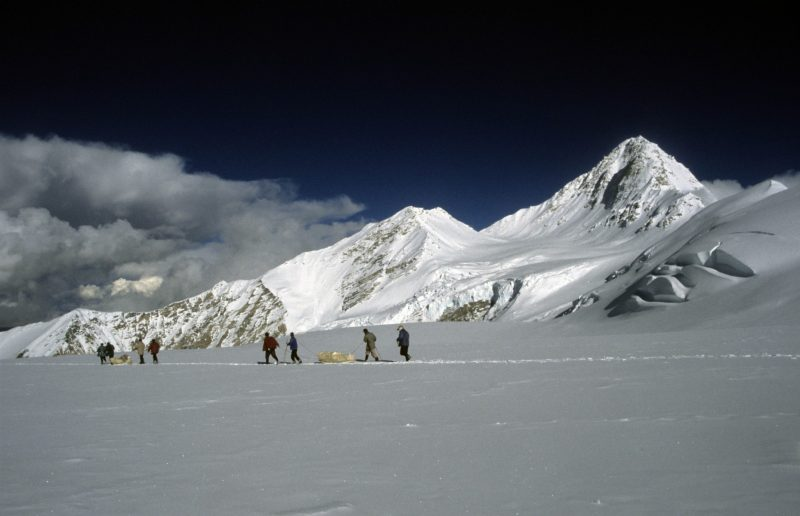 Snow-covered mountaintop with people walking across a snow field in the foreground.