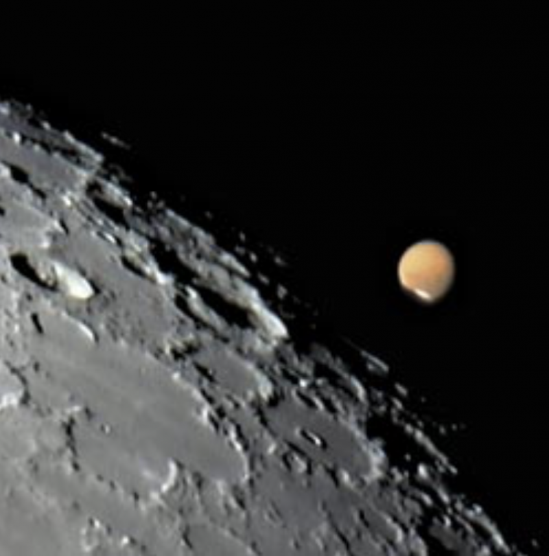 A telescopic view of the moon's cratered limb, with the red disk of Mars disappearing behind it.