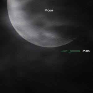Blurry waning moon, nearly hidden by clouds, with faint Mars near the moon's lighted edge.