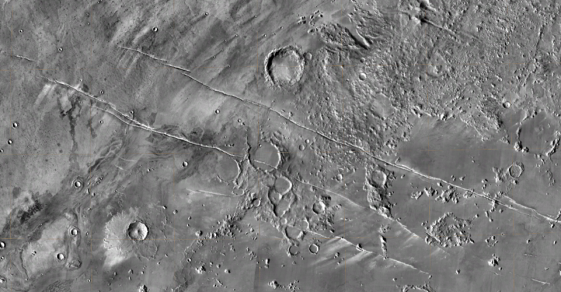 Gray area with a few craters and criss-crossed with scratches.