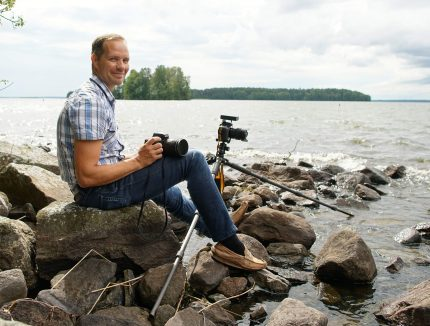 A man with a camera and tripod, seated by a body of water.