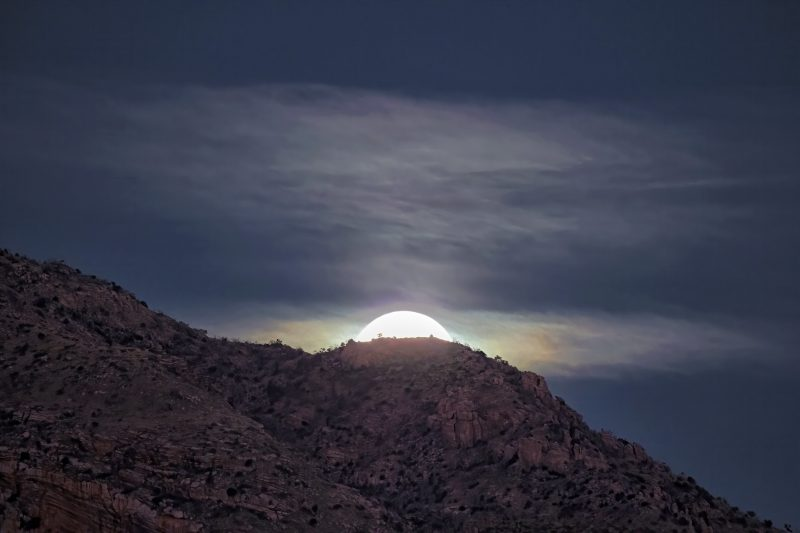 Moon rising above a ridgeline, illuminating clouds with rainbow-like colors.