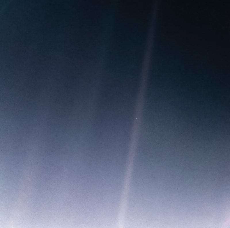An image of bluish space, with streaks of sunlight crossing it, and with a single dot - Earth - within one of the sunbeams.