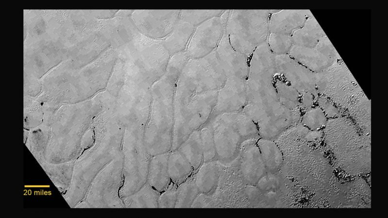 Close-up of an area of Tombaugh Regio. Smooth irregular areas separated by lines.
