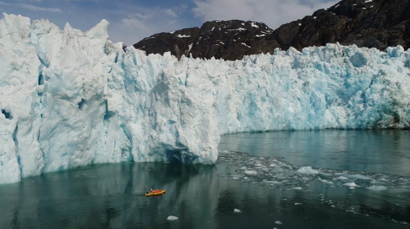 Green water and a huge wall of ice,and a tiny orange kayak.