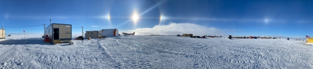 Solar halo and sundogs over Antarctic research camp on vast snow field.