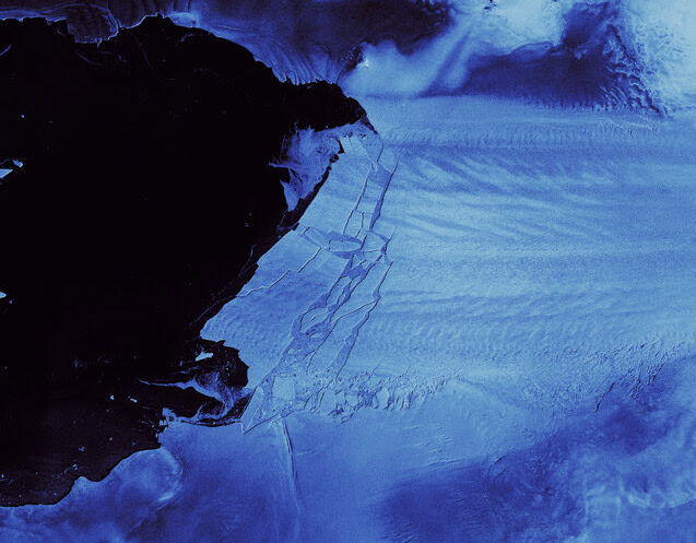 Orbital view, dark ocean water on left, glacier on right with long cracks in it.