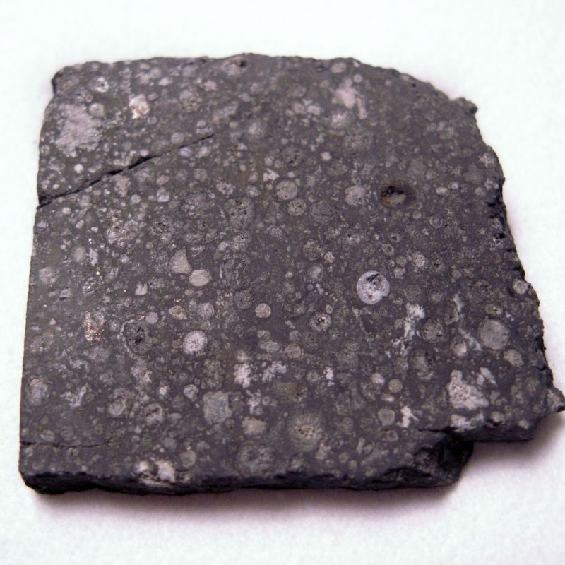 Dark gray rock with lighter-colored spots.