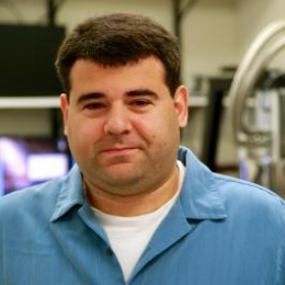 Man in blue shirt with lab equipment behind him.