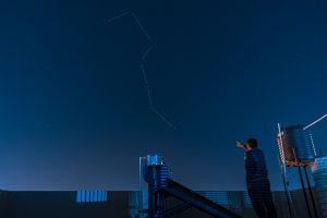 A man on a rooftop points to the Big Dipper.