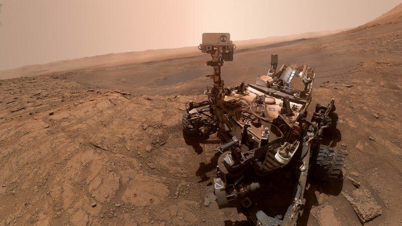 Mechanical wheeled robot in brownish, rocky terrain under pinkish dusty sky.