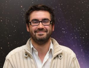 Smiling man with glasses and stars in background.