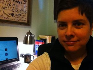 Woman smiling with computer in background.