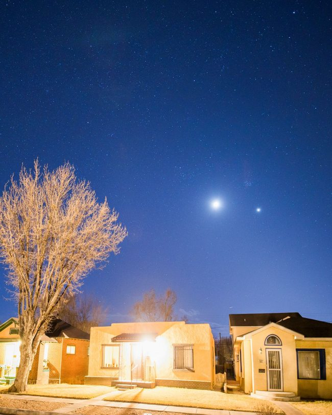 Night sky over brightly lit houses with moon, Venus, and the Pleiades.