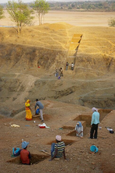 The excavation site, with trenches and people working on-site.