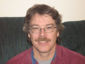 Smiling man with eyeglasses on sofa.