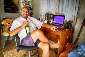 Man lounging in desk chair holding a bottle of whiskey.